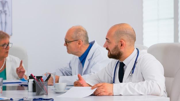 의료 회의를 하는 현대 병원 회의실에서 환자의 문제를 해결하는 의사들의 브레인스토밍 팀워크. 진료소에서 질병의 증상에 대해 이야기하는 의사 팀.
