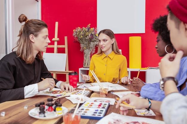 ブレーンストーミングの時間。ブレーンストーミングをしている4人の有望なファッショナブルな若い芸術学生