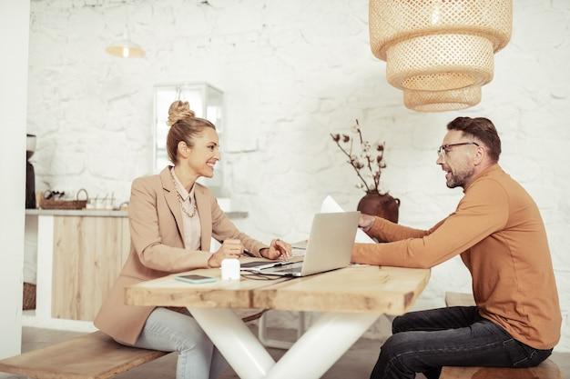 Мозговой штурм. два улыбающихся коллеги сидят за столом и разговаривают в поисках новых дизайнерских идей.