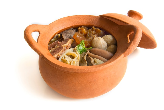 Braised beef clear soup(kaolao nuae toon) in cray pot side view on white background