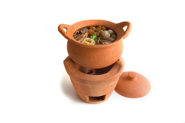 Тушеный суп из говядины (kaolao nuae toon) в cray pot вид сбоку на белом фоне