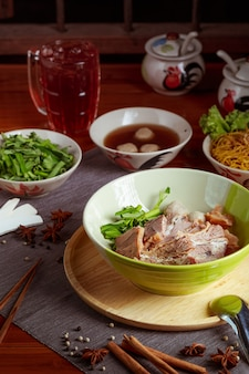 Лапша с тушеной говядиной, тайская еда с гарнирами на столе