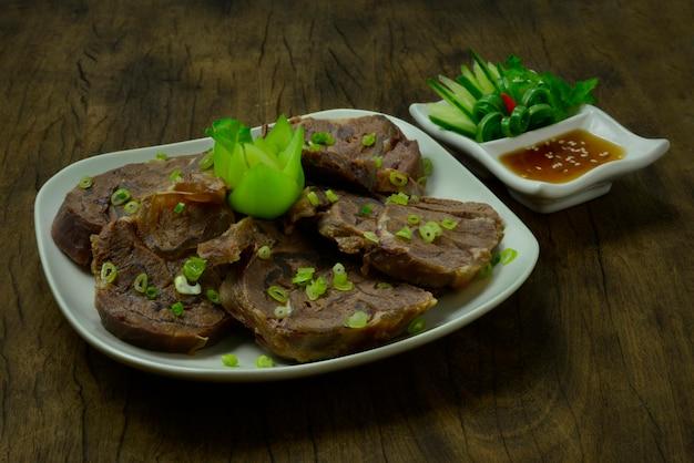 ビーフシャンクの煮込みスライスごま油ソースを添えて、きゅうりと野菜の切り分けを飾る台湾で人気の前菜料理