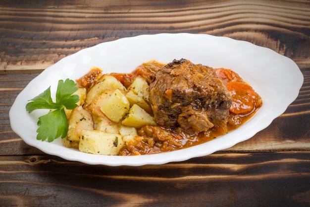 Тушеные говяжьи хвосты с овощами и картофелем в белой тарелке на деревянном фоне.