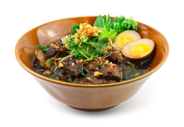 Тушеная говядина с коричневым супом, посыпанная хрустящим чесночным украшением яйцо и овощи, вид сбоку в стиле тайской кухни