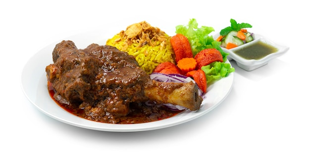 Braised lamb shank biryani rice recipe massaman curry tender and shreddable indian spice and thai food fusion style inside dish with mint sauce sideview