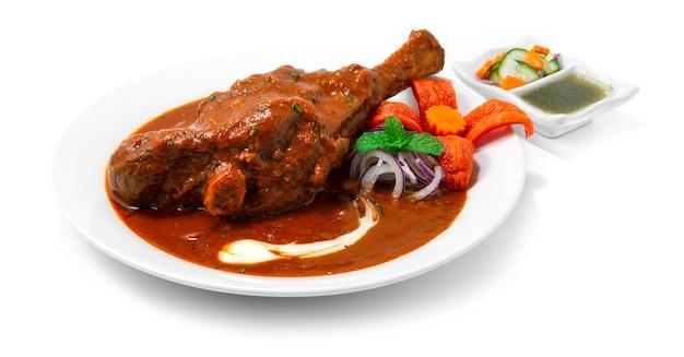 Тушеная рулька ягненка масала карри - это вкусный лук, помидоры, кешью, соус, специя и йогурт, который был медленно приготовлен индийская еда, приправы, блюдо, вид сбоку