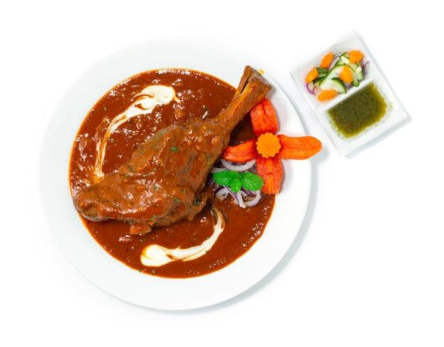Тушеная рулька ягненка масала карри - это вкусный лук, помидоры, кешонут, соус, специя и йогурт, который был медленно приготовлен индийская еда, специи, блюдо, стиль topview