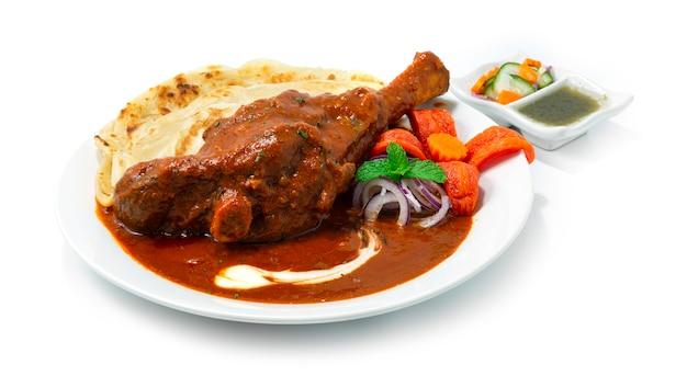 Тушеная рулька ягненка масала карри подается роти - это вкусный лук, помидоры, кешонут, подливка, специи и йогурт, приготовленные медленно, индийская кухня, вид сбоку
