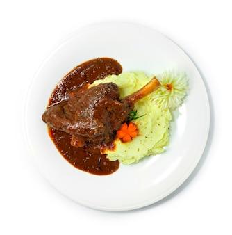 레드 와인 소스, 허브 및 야채를 곁들인 찐 양고기 생크를 부드럽고 잘게 썬 매쉬 포테이토 유럽 음식 스타일 topview