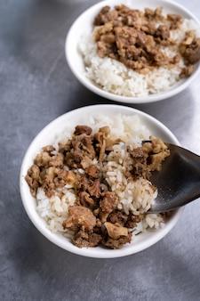 台湾の台南でご飯の上に豚肉を煮込んだ肉ご飯の煮込み。台湾の有名な伝統的な屋台の珍味。旅行のデザインコンセプト、クローズアップ。