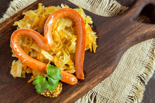 Braised pickled cabbage with grilled sausage in the shape of a heart. on a wooden board