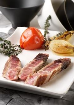 野菜の背景と白いプレートの蒸しマグロ