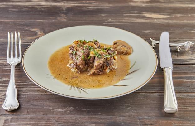 Тушеная телятина с грибами с зеленью в тарелке на деревянных фоне.