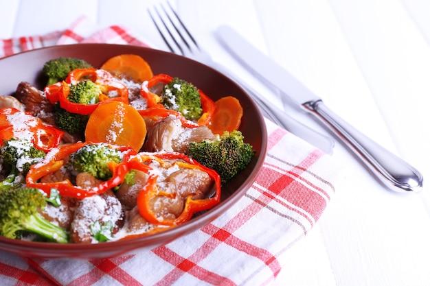 テーブルの上のプレートに野菜とソースで煮込んだ野生のキノコ