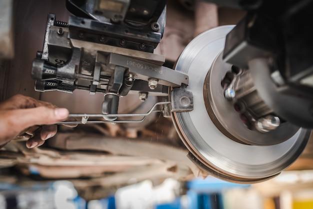 Brake disc grinding machine - vehicle brake-disc turning machine. automobile disc brake system repair in garage.