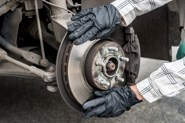 Brake disk with worker's hands in gloves close up