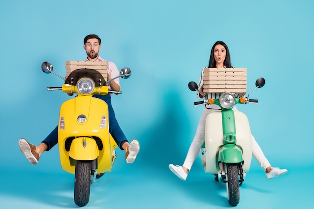 Brakes failed! full length photo of crazy open mouth lady guy drive two vintage moped hold many paper pizza boxes courier profession isolated blue color wall