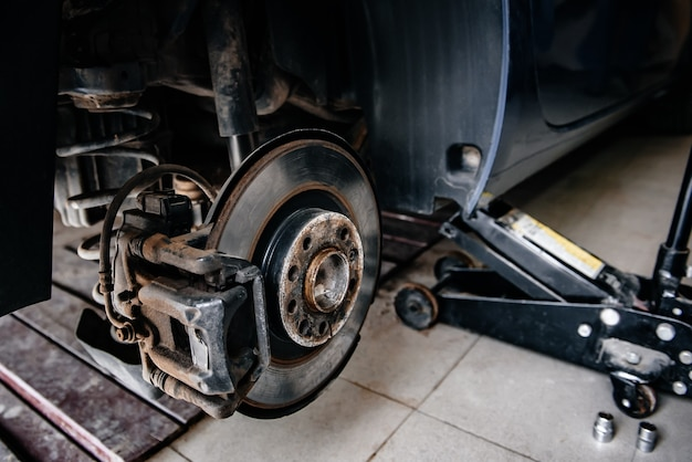 브레이크 디스크와 브레이크 패드가 있는 제동 시스템 자동차. 차고에서 자동차 정지 수리.