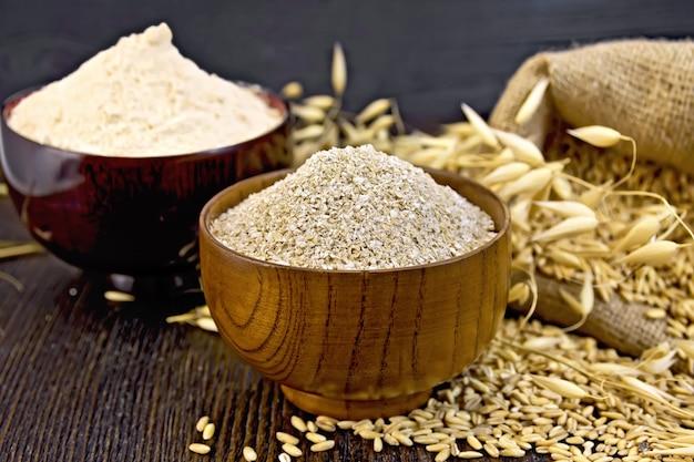 ふすまフレークオーツ麦とオーテン粉を2つの木製ボウルに入れ、穀物オーツ麦の袋、暗い木の板に耳を当てる