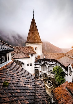 霧の山の背景にブランルーマニア11月ブラン城の屋根