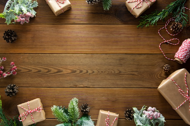 クリスマスフレーム、モックアップ、冬の休日の背景。松ぼっくり、モミbrances、茶色の木のテーブルの上のクリスマスギフトボックス。クリスマスレイアウト、コピースペース。