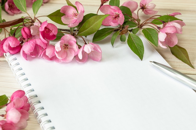 A branch of a blossoming apple tree and a blank notebook on a wooden table. copy space