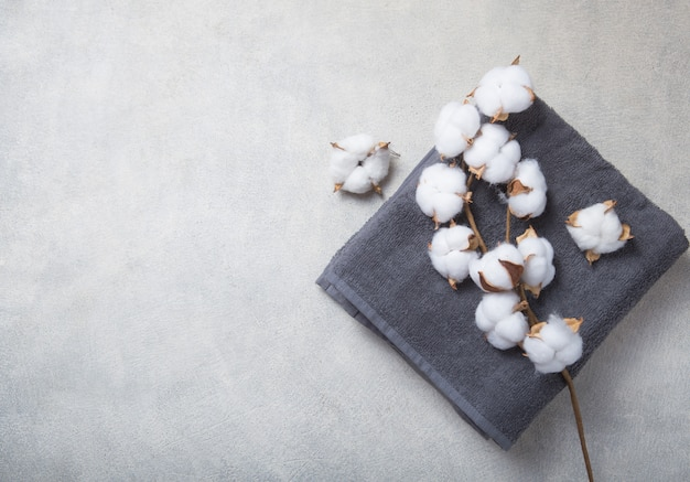 Branch of cotton and baige grey  towels on concrete background.