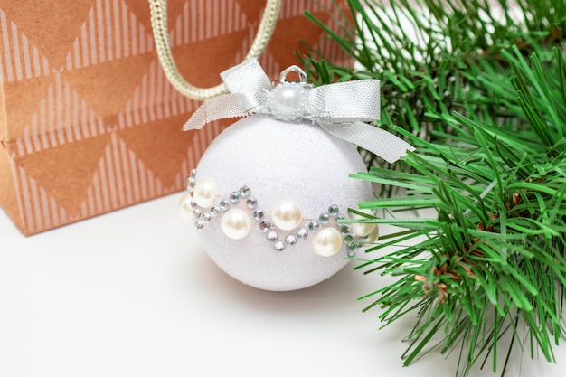 Branch of fir pine tree, shiny decorative christmas ball and paper bag
