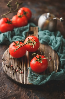 Branch of fresh ripe tomatoes on cutting board
