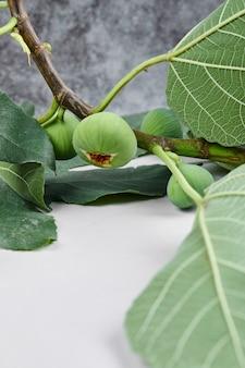 Un ramo di fichi verdi con foglie su marmo.