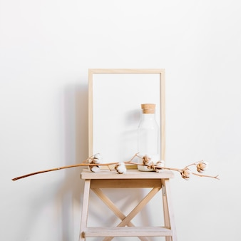 Branch in front of frame on stool