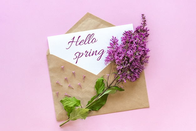 Branch of lilac on craft envelope with white empty paper card for text, pink background. greeting card flat lay mock up