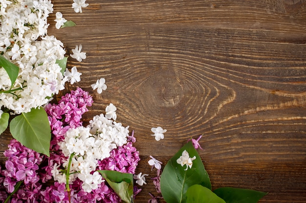 Branch of lilac lying on a brown wooden background.