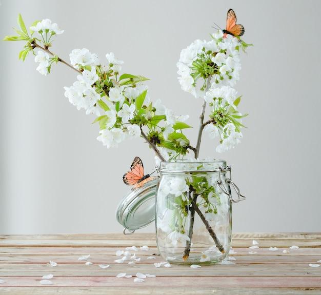 木製のガラスの瓶に蝶と桜の枝