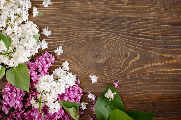 Ветвь сирени лежа на коричневой деревянной предпосылке.