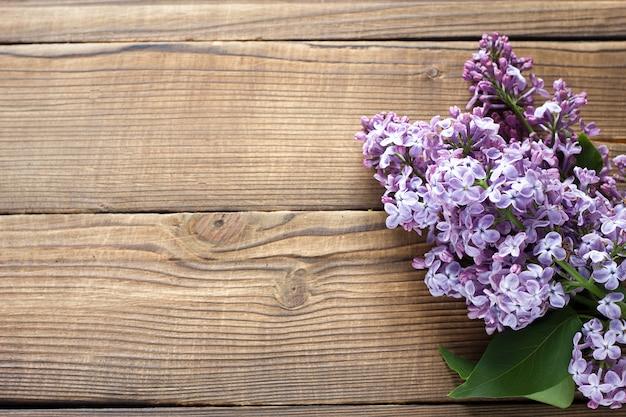 木製の背景に紫のライラックの枝