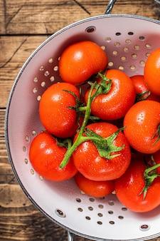 Филиал красных помидоров черри на дуршлаге. деревянный фон. вид сверху.