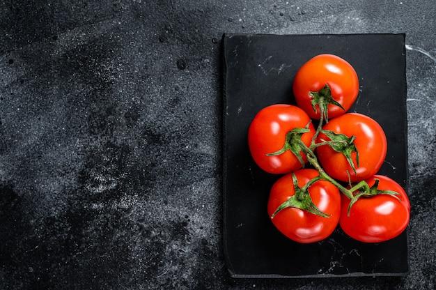 Филиал красных помидоров черри на мраморной доске. черный фон. вид сверху. скопируйте пространство.