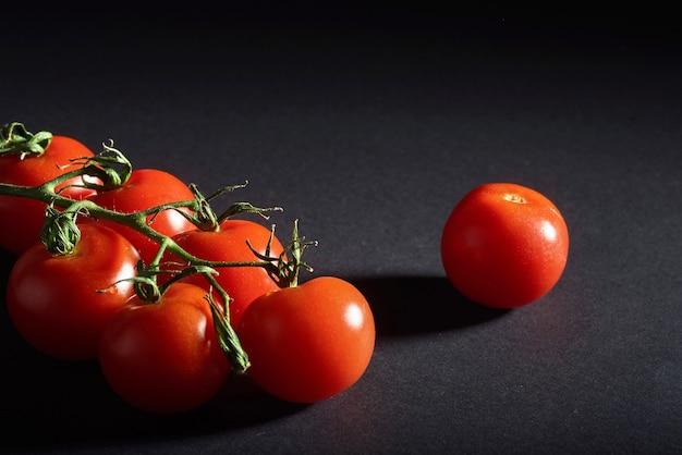 Филиал красных органических помидоров на черном