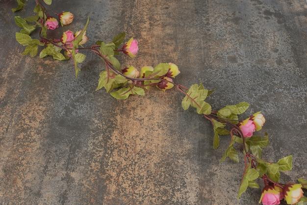 大理石の表面に赤いバラの枝。