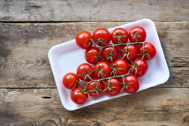Отделение спелых помидоров черри в пластиковой упаковке