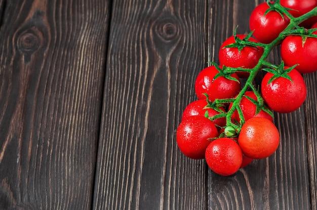 Филиал спелых, свежих помидоров черри на темной деревянной поверхности