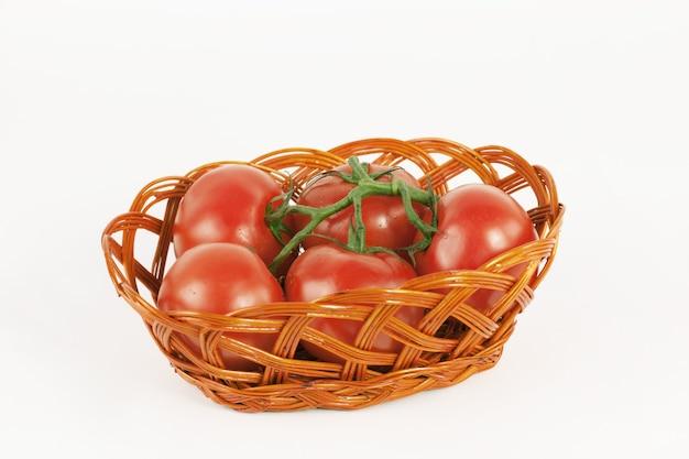 枝編み細工品バスケットの完熟トマトの枝。白で隔離。コピースペース付きの写真