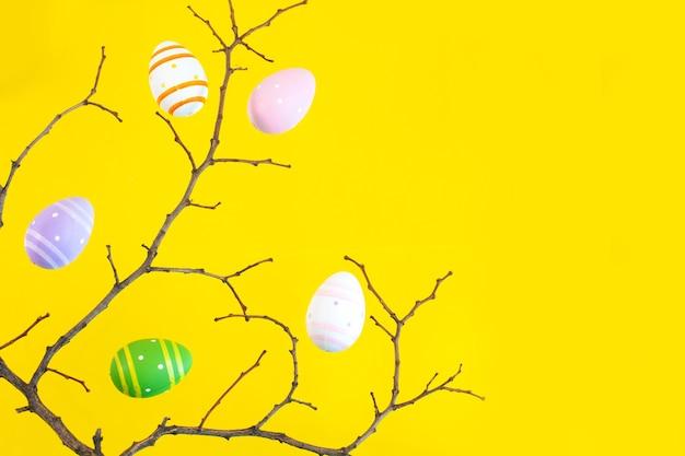 木の枝と黄色い机の上のカラフルなイースターエッグ