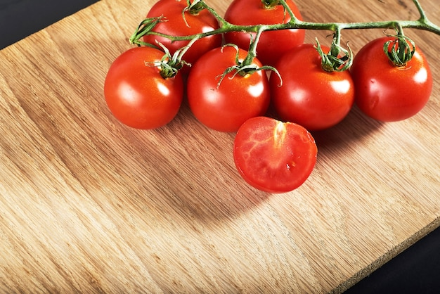 Branch of red cherry tomatoes organic wooden.