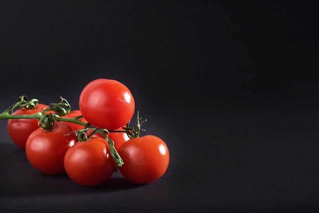 Branch of red organic tomatoes on a black