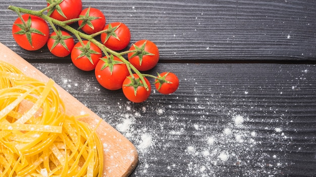 Branch of ripe cherry tomatoes with raw tagliatelle dusted with flour on wooden backdrop