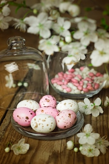 Branch of spring flowers and colorful pink candy eggs for easter on rustic