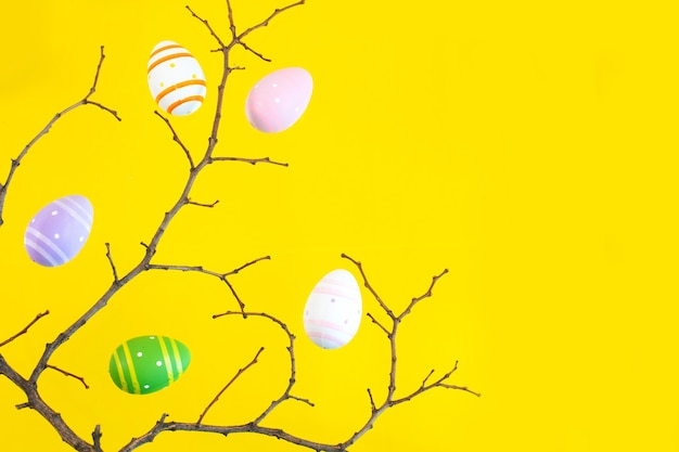 Branch of tree and colorful easter eggs on a yellow desk